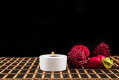 Σκηνή SPA - aromatherapy κερί και λουλούδι σε ένα μαύρο backgroun Στοκ Φωτογραφία