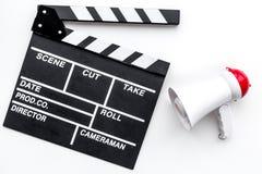 Σκηνοθέτης, έννοια παραγωγών μαγνητοσκόπηση Ηλεκτρονικό megaphone και clapperbord στην άσπρη τοπ άποψη υποβάθρου στοκ εικόνες