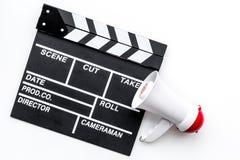 Σκηνοθέτης, έννοια παραγωγών μαγνητοσκόπηση Ηλεκτρονικό megaphone και clapperbord στην άσπρη τοπ άποψη υποβάθρου Στοκ Εικόνα