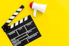 Σκηνοθέτης, έννοια παραγωγών μαγνητοσκόπηση Ηλεκτρονικό megaphone και clapperbord στο κίτρινο διάστημα άποψης υποβάθρου τοπ για Στοκ εικόνα με δικαίωμα ελεύθερης χρήσης