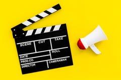 Σκηνοθέτης, έννοια παραγωγών μαγνητοσκόπηση Ηλεκτρονικό megaphone και clapperbord στο κίτρινο διάστημα άποψης υποβάθρου τοπ για στοκ εικόνες