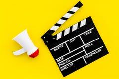 Σκηνοθέτης, έννοια παραγωγών μαγνητοσκόπηση Ηλεκτρονικό megaphone και clapperbord στο κίτρινο διάστημα άποψης υποβάθρου τοπ για στοκ φωτογραφία με δικαίωμα ελεύθερης χρήσης