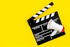 Σκηνοθέτης, έννοια παραγωγών μαγνητοσκόπηση Ηλεκτρονικό megaphone και clapperbord στο κίτρινο διάστημα άποψης υποβάθρου τοπ για Στοκ Εικόνα