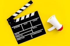 Σκηνοθέτης, έννοια παραγωγών μαγνητοσκόπηση Ηλεκτρονικό megaphone και clapperbord στην κίτρινη τοπ άποψη υποβάθρου στοκ εικόνα με δικαίωμα ελεύθερης χρήσης