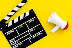 Σκηνοθέτης, έννοια παραγωγών μαγνητοσκόπηση Ηλεκτρονικό megaphone και clapperbord στην κίτρινη τοπ άποψη υποβάθρου Στοκ Εικόνες