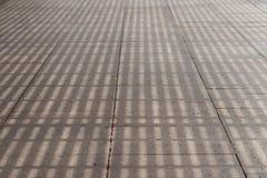 Σκιά από μια πέργκολα σε ένα οδικό κεραμίδι Στοκ φωτογραφία με δικαίωμα ελεύθερης χρήσης