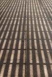 Σκιά από μια πέργκολα σε ένα οδικό κεραμίδι Στοκ Φωτογραφίες
