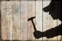 Σκιά ενός ατόμου με το σφυρί στο φυσικό ξύλινο υπόβαθρο Στοκ εικόνες με δικαίωμα ελεύθερης χρήσης
