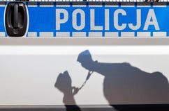 Σκιά ενός ατόμου στις χειροπέδες σε ένα περιπολικό της Αστυνομίας. στοκ εικόνες