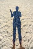 Σκιά της γυναίκας στην παραλία που παρουσιάζει το σημάδι της ειρήνης Στοκ φωτογραφία με δικαίωμα ελεύθερης χρήσης