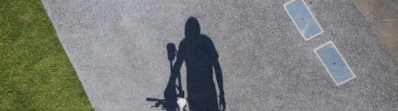 Σκιά του αρσενικού bicyclist που περπατά στο αστικό περιβάλλον Στοκ Φωτογραφίες