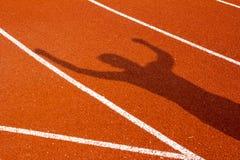 Σκιά του ατόμου σε μια τρέχοντας πορεία σταδίων απομονωμένο έννοια αθλητικό λευκό Στοκ Εικόνες