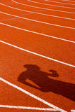 Σκιά του ατόμου στην κόκκινη τρέχοντας διαδρομή απομονωμένο έννοια αθλητικό λευκό Στοκ Εικόνες
