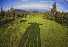 Σκιά των φίλων μεταξύ του φανταστικά όμορφου τοπίου στο υπόβαθρο των Καρπάθιων βουνών στοκ φωτογραφίες