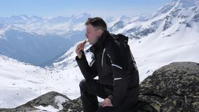 Σκιέρ ατόμων που τρώει ένα μεσημεριανό γεύμα σάντουιτς στο χιονοδρομικό κέντρο βουνών απόθεμα βίντεο