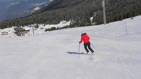 Σκιέρ που κάνει σκι κάτω από τη γλυπτική στην κλίση στα βουνά στο χειμερινό χιονοδρομικό κέντρο απόθεμα βίντεο