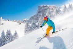 Σκιέρ που κάνει σκι προς τα κάτω στα υψηλά βουνά στοκ εικόνες