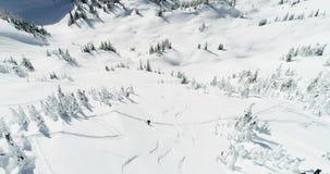 Σκιέρ που κάνουν σκι σε ένα καλυμμένο χιόνι βουνό 4k απόθεμα βίντεο