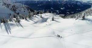 Σκιέρ που ρίχνουν το χιόνι προς τα πάνω σε ένα καλυμμένο χιόνι βουνό 4k απόθεμα βίντεο