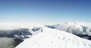 Σκιέρ που στέκεται στην κορυφή καλυμμένου του χιόνι βουνού 4k απόθεμα βίντεο