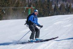 Σκιέρ στα χειμερινά βουνά την ηλιόλουστη ημέρα Στοκ Φωτογραφία