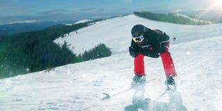 Σκιέρ στο κράνος και γυαλιά που οδηγούν έναν λόφο χιονιού στοκ εικόνα με δικαίωμα ελεύθερης χρήσης