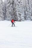 Σκιέρ στο κόκκινο σακάκι στην κίνηση που έρχεται κάτω από το ίχνος βουνών Στοκ φωτογραφία με δικαίωμα ελεύθερης χρήσης