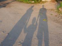 Σκιές της μητέρας και του πατέρα που κρατούν το χέρι του μικρού μωρού τους στο έδαφος στοκ φωτογραφία με δικαίωμα ελεύθερης χρήσης