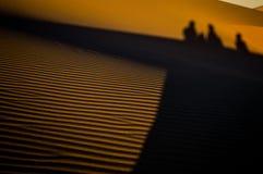 Σκιές τριών ανθρώπων †«που αναρριχούνται στο μεγάλο αμμόλοφο μπαμπάδων στην ανατολή Στοκ φωτογραφία με δικαίωμα ελεύθερης χρήσης