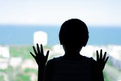 Σκιαγραφήστε ένα μικρό αγόρι που εξετάζει θάλασσα το παράθυρο στοκ εικόνες