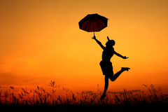 Σκιαγραφία άλματος και ηλιοβασιλέματος γυναικών ομπρελών Στοκ εικόνες με δικαίωμα ελεύθερης χρήσης