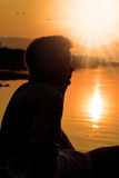 Σκιαγραφία αγοριών, ηλιοβασίλεμα στη λίμνη Στοκ Εικόνες