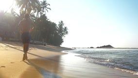 Σκιαγραφία αθλητικών τύπων αναμμένη από τα τρεξίματα ήλιων κατά μήκος της αμμώδους ακτής φιλμ μικρού μήκους