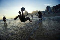 Σκιαγραφία λακτίσματος ποδηλάτων που παίζει το ποδόσφαιρο Ρίο παραλιών Altinho Στοκ εικόνες με δικαίωμα ελεύθερης χρήσης