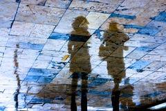 Σκιαγραφία αντανάκλασης της νέας γυναίκας δύο μια βροχερή ημέρα στοκ φωτογραφίες