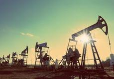Σκιαγραφία αντλιών πετρελαίου ενάντια στον ήλιο - εκλεκτής ποιότητας αναδρομικό ύφος Στοκ φωτογραφία με δικαίωμα ελεύθερης χρήσης