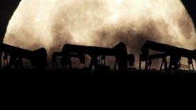 Σκιαγραφία αντλιών πετρελαίου σε ένα υπόβαθρο πανσελήνων σε ένα μολυσμένο περιβάλλον απόθεμα βίντεο