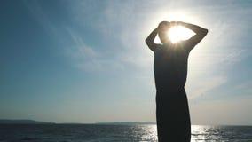 Σκιαγραφία ατόμων που κάνει την άσκηση γιόγκας στην παραλία ηλιοβασιλέματος απόθεμα βίντεο
