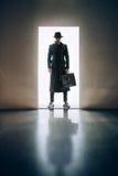 Σκιαγραφία ατόμων που στέκεται λαμβάνοντας υπόψη το άνοιγμα της πόρτας στο σκοτεινό roo Στοκ εικόνες με δικαίωμα ελεύθερης χρήσης