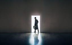 Σκιαγραφία ατόμων που στέκεται λαμβάνοντας υπόψη το άνοιγμα της πόρτας στο σκοτεινό roo Στοκ Φωτογραφία