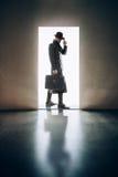 Σκιαγραφία ατόμων που στέκεται λαμβάνοντας υπόψη το άνοιγμα της πόρτας στο σκοτεινό roo Στοκ φωτογραφία με δικαίωμα ελεύθερης χρήσης