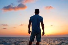 Σκιαγραφία ατόμων στο ηλιοβασίλεμα κοντά στη θάλασσα στοκ εικόνες