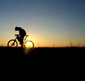 σκιαγραφία βουνών κοριτσιών ποδηλατών Στοκ Φωτογραφίες