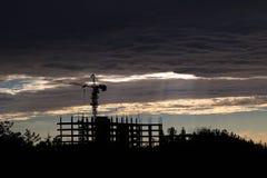 Σκιαγραφία γερανών κατασκευής στα σύννεφα Στοκ εικόνες με δικαίωμα ελεύθερης χρήσης