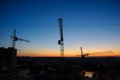 Σκιαγραφία γερανών πύργων στο εργοτάξιο οικοδομής Στοκ Εικόνα