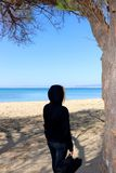 Σκιαγραφία γυναικών που περπατά στην παραλία με την κιθάρα στη μαύρη κουκούλα στοκ φωτογραφίες