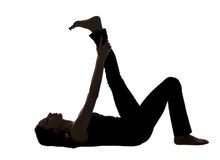 Σκιαγραφία γυναικών, τέντωμα ποδιών ξαπλώματος στη γιόγκα Στοκ εικόνα με δικαίωμα ελεύθερης χρήσης
