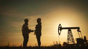 Σκιαγραφία δύο μηχανικοί που τινάζουν τα χέρια στο υπόβαθρο μια αντλία πετρελαίου στο ηλιοβασίλεμα Βιομηχανικός, έννοια πετρελαίο απόθεμα βίντεο