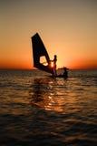 Σκιαγραφία εκμάθησης Windsurfer ενάντια στον ήλιο Στοκ εικόνες με δικαίωμα ελεύθερης χρήσης