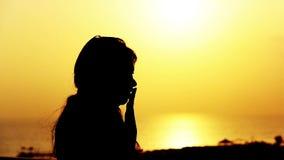 Σκιαγραφία ενός αγαπώντας ζεύγους, φιλί της θάλασσας στο ηλιοβασίλεμα φιλμ μικρού μήκους